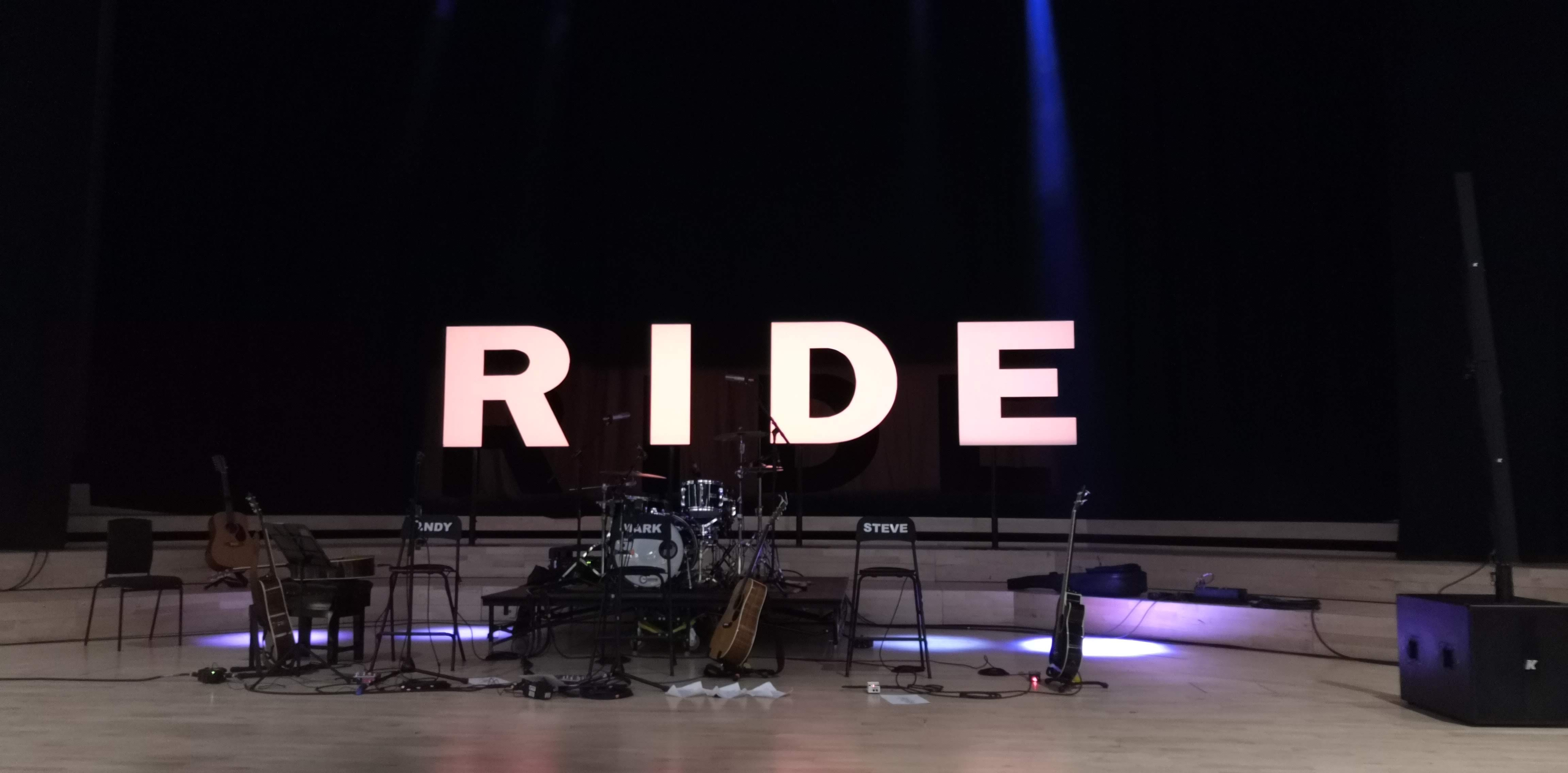 Instruments on stage with illuminated Ride logo. Ride @ Royal Northern College of Music